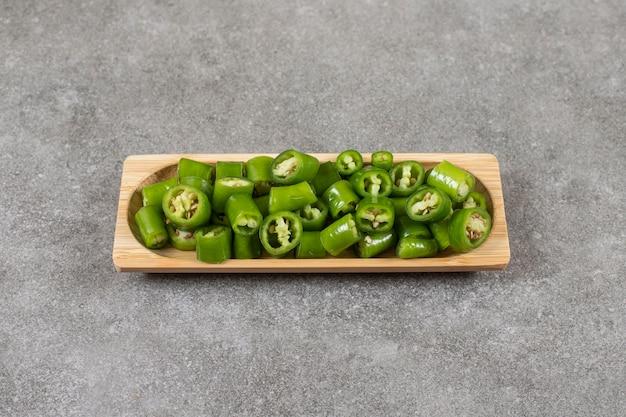 Gesneden hete peper in een kom, op de marmeren tafel.