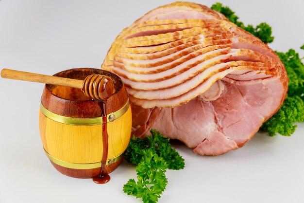 Gesneden hickory gerookte ham met honing in houten pot.