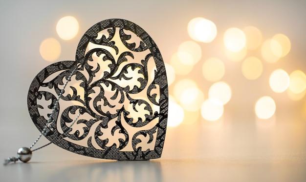 Gesneden houten hart op een grijze achtergrond met een gouden bokeh en kopieer de ruimte