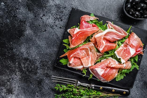Gesneden jamon serrano varkensvlees ham vlees op een marmeren bord. zwarte achtergrond. bovenaanzicht. ruimte kopiëren.