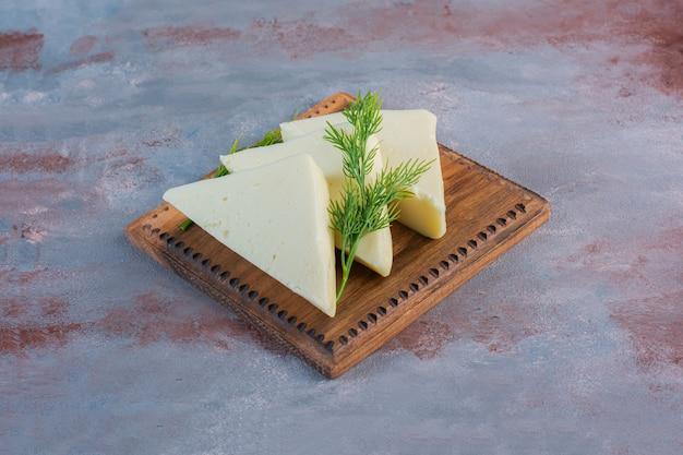 Gesneden kaas en dille op een bord close-up, op de marmeren achtergrond.