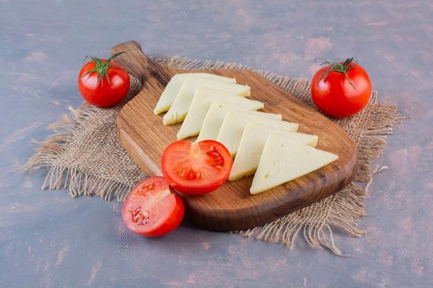 Gesneden kaas en tomaten op een snijplank op een jute servet, op de marmeren achtergrond.