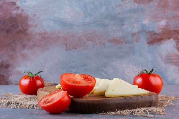 Gesneden kaas en tomaten op een snijplank op een jute servet op het marmeren oppervlak