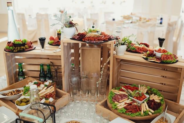 Gesneden kaas en vlees geserveerd op bord met olivas staan op houten dozen