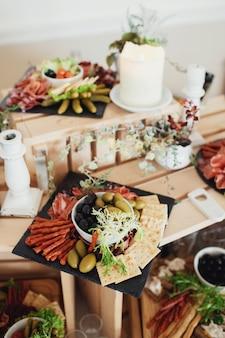 Gesneden kaas en vlees geserveerd op bord met olivas