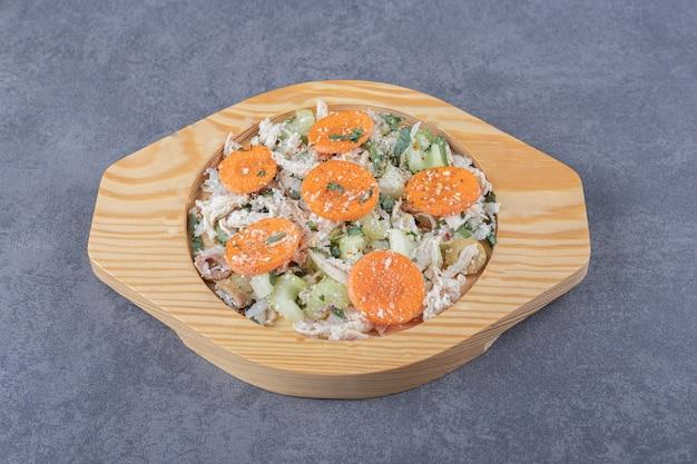 Gesneden kip met wortelen op houten plaat.