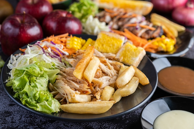 Gesneden kippenbiefstuk met brood, wortelen, bloemkool, rapen en maïs op een zwarte plaat.