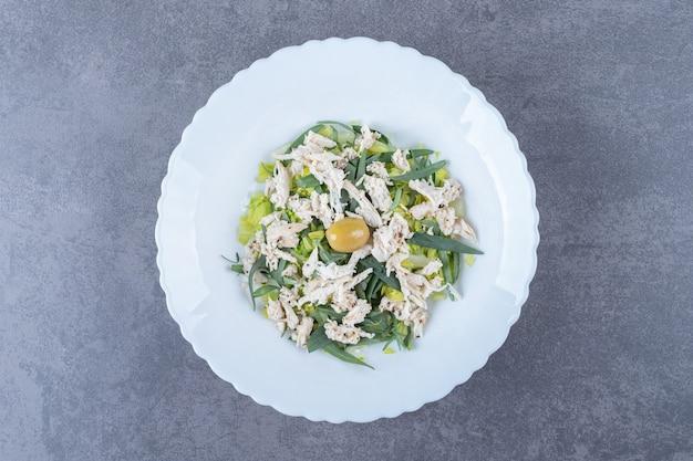 Gesneden kippensalade op witte plaat.