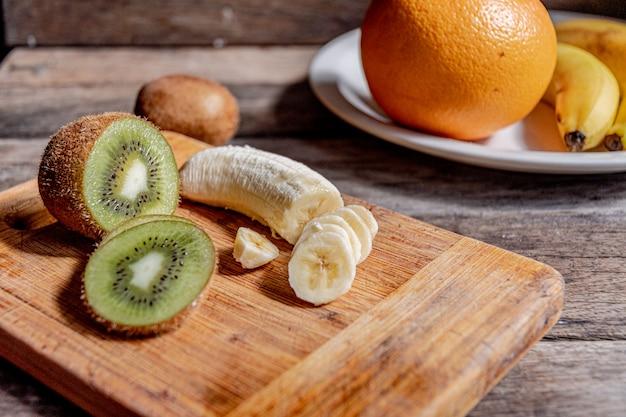 Gesneden kiwi en banaan op het bord van de keuken op de achtergrond van grapefruit en bananen in een plaat. het koken van fruitsalade in de huiskeuken.