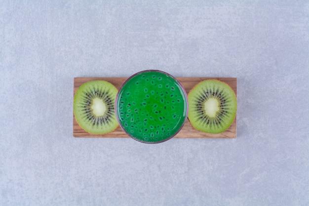Gesneden kiwi en kiwisap op een bord op marmeren tafel.