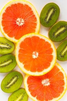 Gesneden kiwi en sinaasappelen op een witte achtergrond