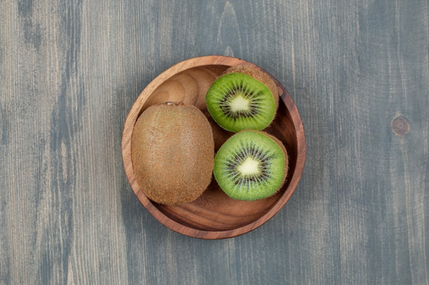Gesneden kiwi met hele kiwi op een houten tafel