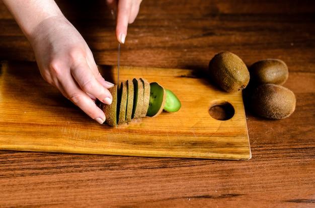 Gesneden kiwi op een houten bord.