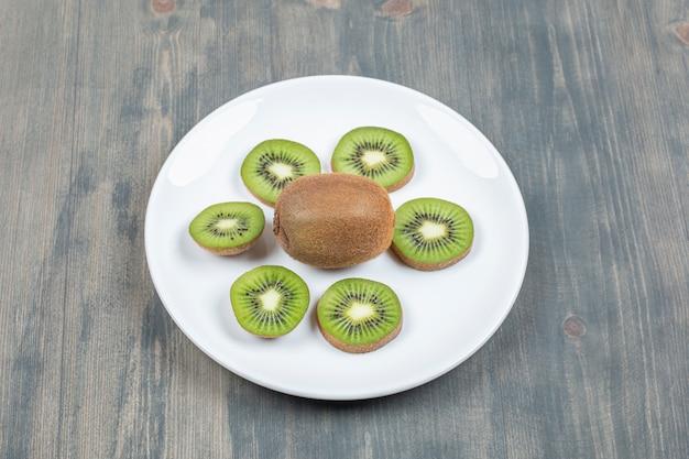 Gesneden kiwi's geïsoleerd op een witte plaat