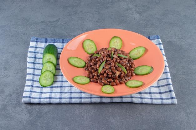 Gesneden komkommer en bonen op een bord op een handdoek, op het marmeren oppervlak.