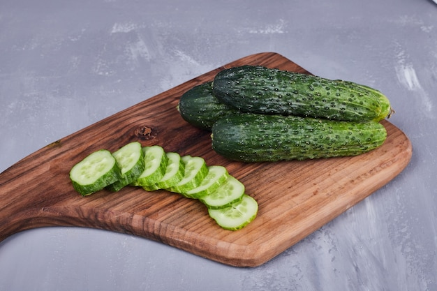 Gesneden komkommer of augurken op een houten bord, bovenaanzicht.