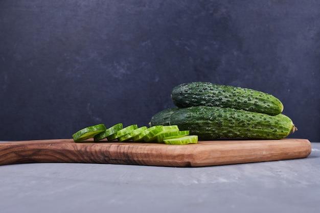 Gesneden komkommer of augurken op een houten bord.