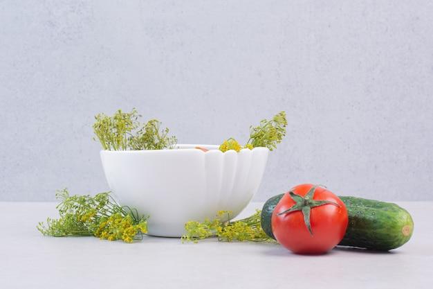 Gesneden komkommers en tomaten in witte kom met greens
