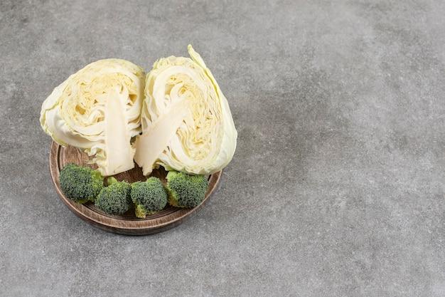 Gesneden kool en broccoli op een bord op een bord, op de marmeren tafel.