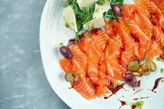 Gesneden licht gezouten zalm met rucola en parmezaan. rode vissashimi met kappertjes en olijven op een witte plaat. vers zee-eten