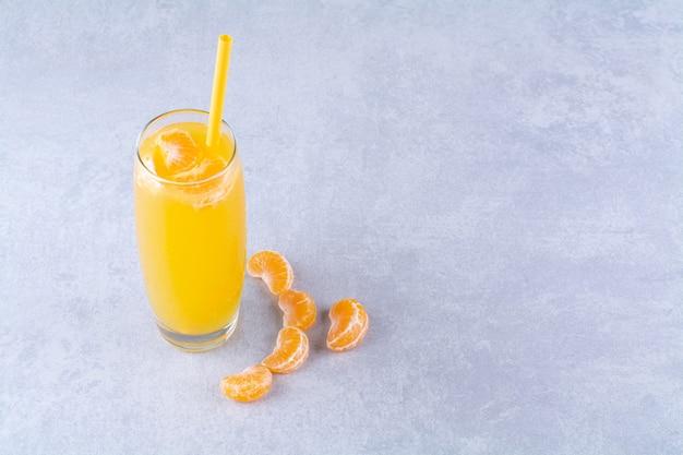 Gesneden mandarijn en een glas sappig, op de marmeren achtergrond.