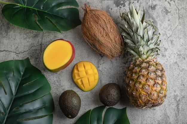 Gesneden mango, kokosnoot, ananas en rijpe avocado's op marmeren oppervlak.