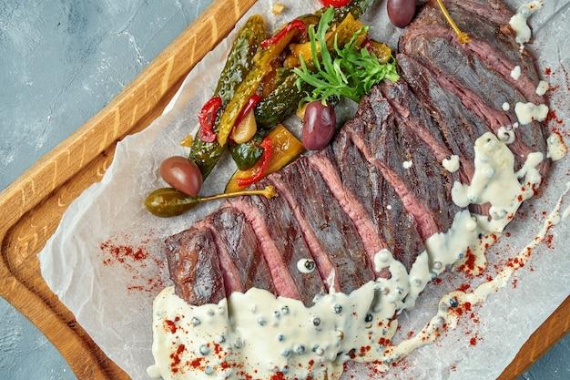 Gesneden medium rare biefstuk met ingelegde komkommersalade op perkament. bovenaanzicht. kopieer ruimte