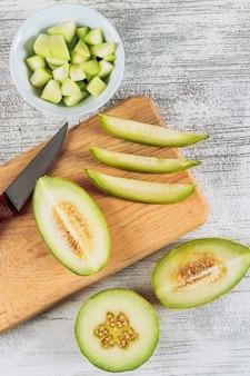 Gesneden meloen in een houten snijplank met meloen in kom en mes plat lag op een witte stenen achtergrond