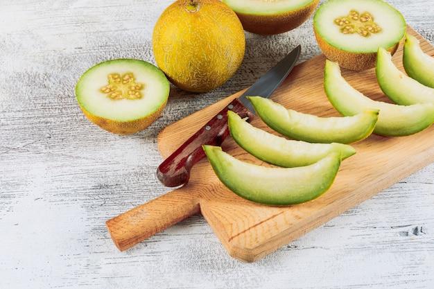 Gesneden meloen in een houten snijplank met verdeeld in halve meloen hoge hoek uitzicht op een witte stenen achtergrond