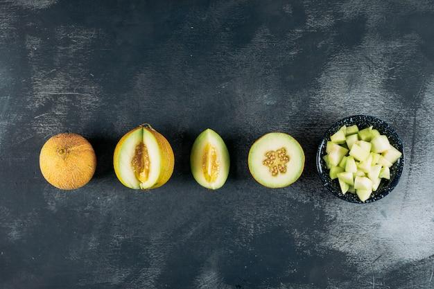 Gesneden meloenen met meloen in een zwarte kom bovenaanzicht op een donkere houten achtergrond kopie ruimte voor tekst