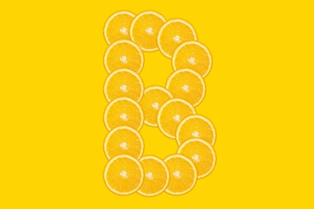 Gesneden oranje alfabet - letter b. gele achtergrond. vers gezond oranje fruit. sappige lettertype.