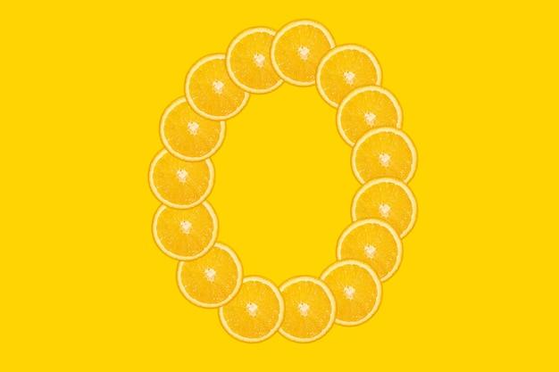 Gesneden oranje alfabet - letter o. gele achtergrond. vers gezond oranje fruit. sappige lettertype.