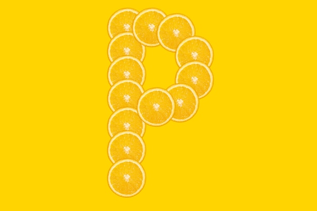 Gesneden oranje alfabet - letter p. gele achtergrond. vers gezond oranje fruit. sappige lettertype.