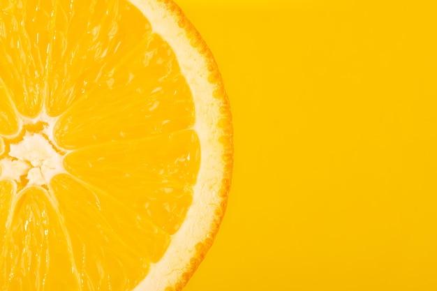 Gesneden oranje, gele achtergrond, kopieer ruimte. vers, sappig fruit, bron van vitamine c. heldere achtergrond.