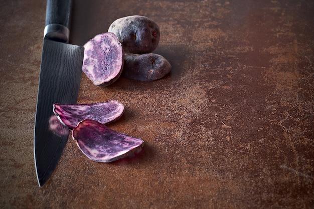 Gesneden paarse aardappeltjes, twee plakjes mes en twee hele aardappelen op donker