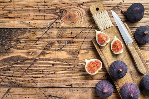 Gesneden paarse vijgen op een snijplank. houten tafel. bovenaanzicht.