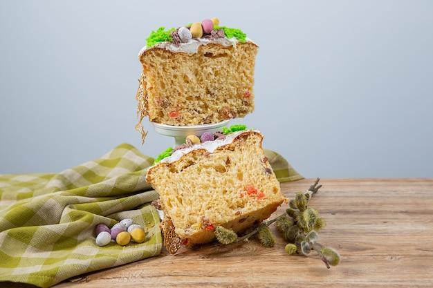 Gesneden paascake gemaakt van gistdeeg, versierd met eetbaar mos met een nest en chocolade-eieren. het poreuze oppervlak van de cake
