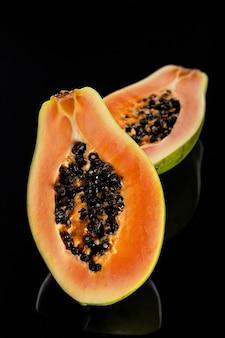 Gesneden papaya op zwart glanzend oppervlak