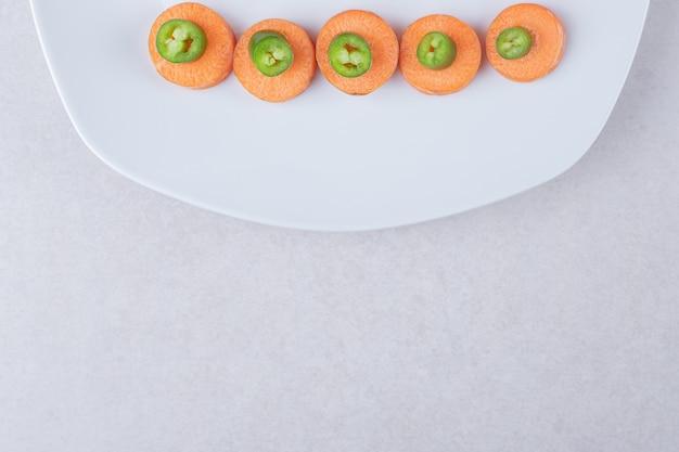 Gesneden paprika op wortel naast tomaten op plaat op marmeren tafel.