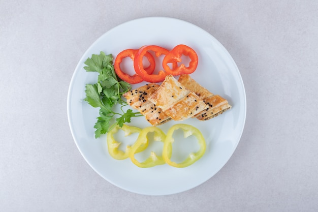 Gesneden paprika, peterselie en pannenkoeken met vlees op plaat, op het marmer.