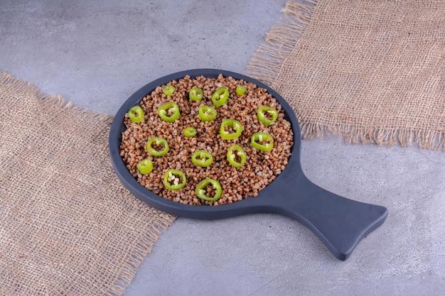 Gesneden paprika's bovenop een portie boekweit in een koekenpan op marmeren achtergrond. hoge kwaliteit foto