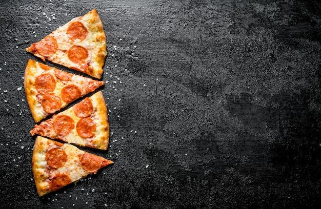 Gesneden pepperonispizza met kaas en salami. op zwarte rustieke achtergrond