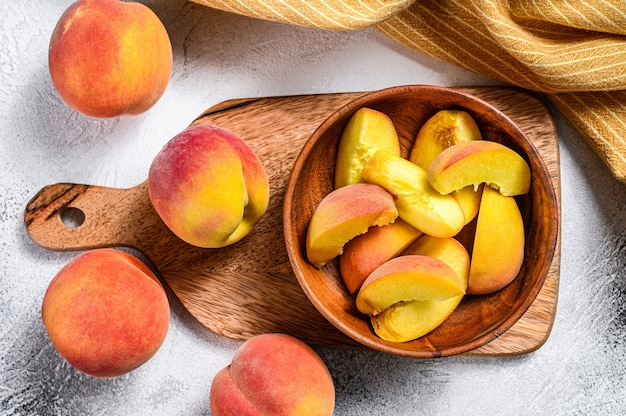 Gesneden perziken, biologisch fruit in een houten kom.