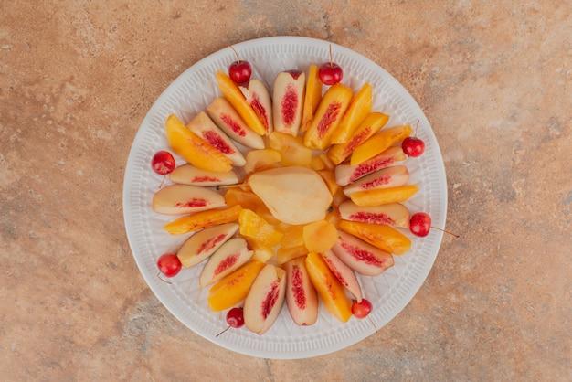 Gesneden perziken op marmeren tafel versierd met kersen.
