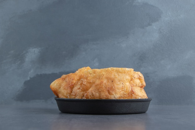 Gesneden piroshki met aardappelen in zwarte kom.
