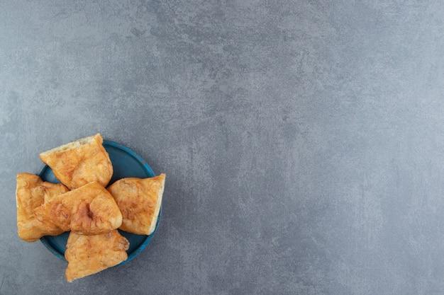 Gesneden piroshki met aardappelen op blauw bord.