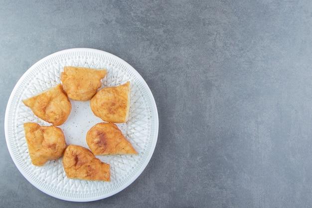 Gesneden piroshki met aardappelen op witte plaat.