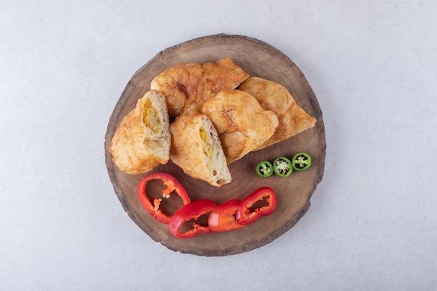 Gesneden pirozhki en paprika aan boord op marmeren tafel.