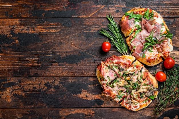 Gesneden pizza met prosciutto parmaham, rucola en parmezaanse kaas. donkere houten achtergrond. bovenaanzicht. kopieer ruimte.