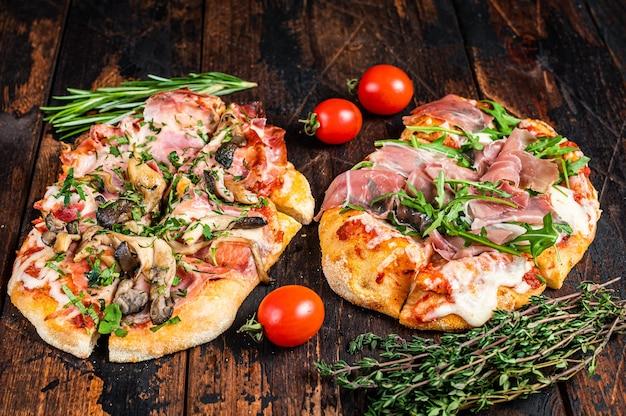 Gesneden pizza met prosciutto parmaham, rucola en parmezaanse kaas. donkere houten achtergrond. bovenaanzicht.